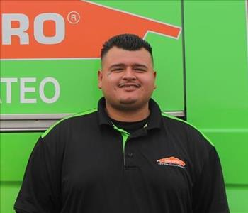 Male employee with black hair smiling in front of our SERVPRO San Mateo vehicle