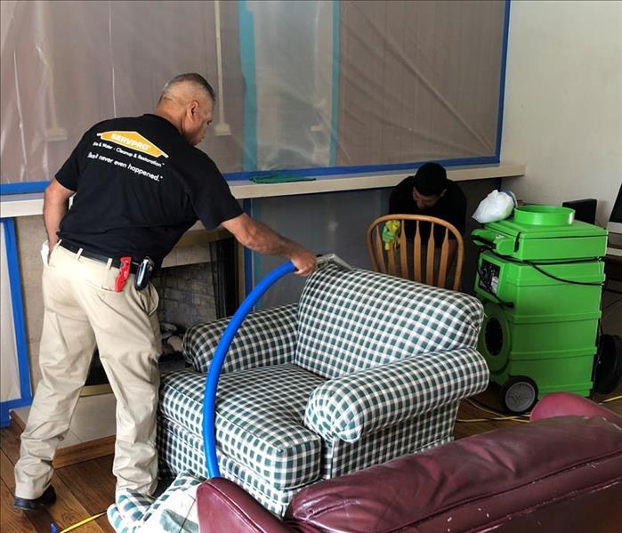 technician deep cleaning a sofa from San Mateo home.